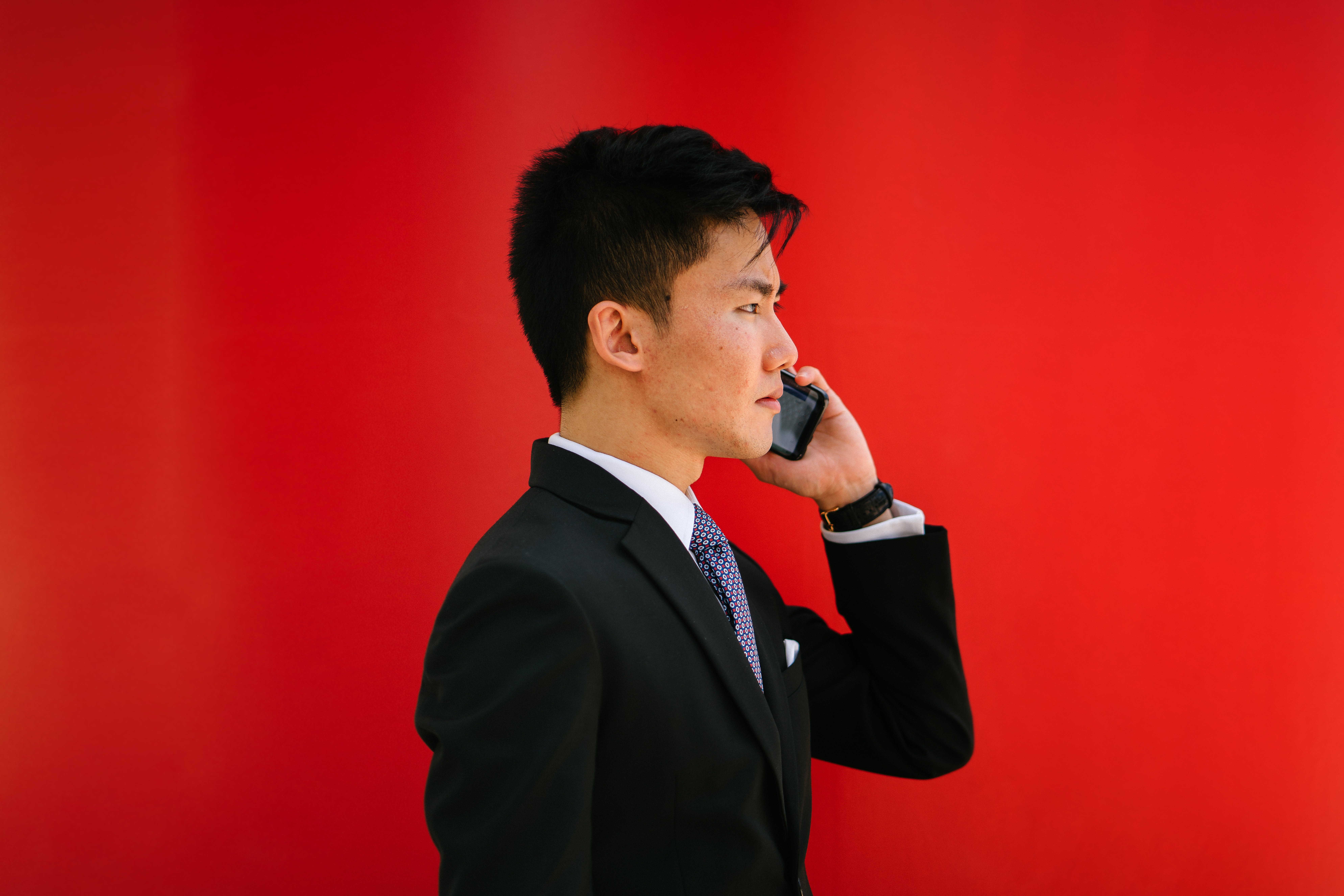 businessman-on-phone-red-background